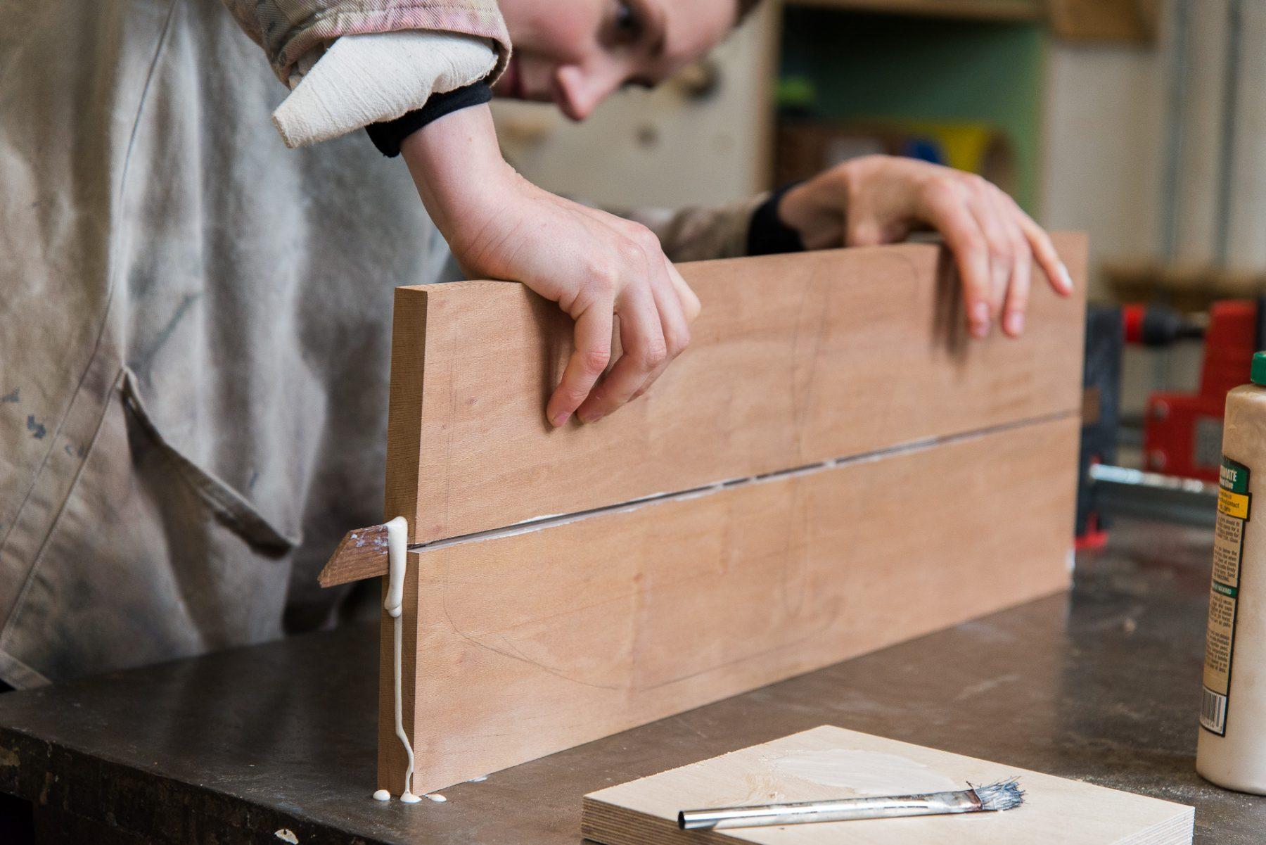 Woodwork student gluing boards in workshop